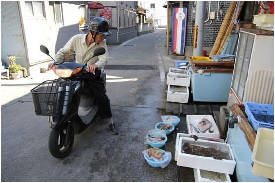原付に乗ったまま魚の品定めをする男性