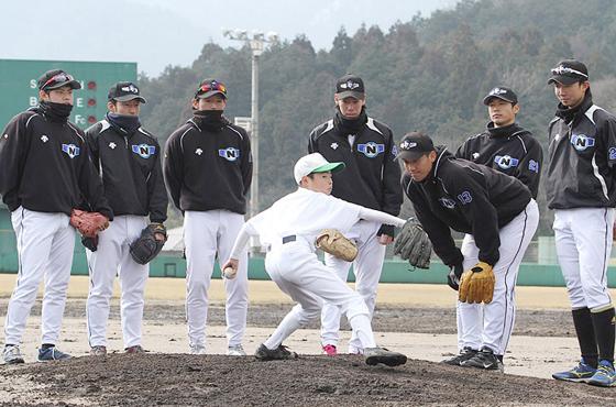 球場で少年を指導する選手たち