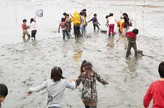 ため池で泥だらけになる子どもたち