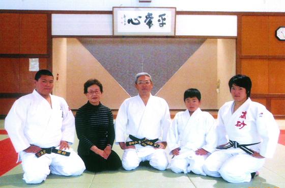 写真:柔道着を着こみ、道場に座る大辻さんとご家族