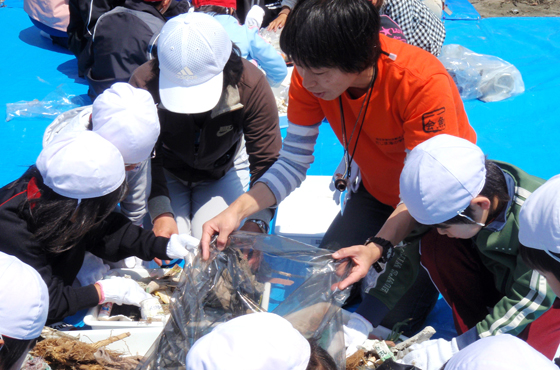 写真:子ども達に海で拾ったゴミを見せている