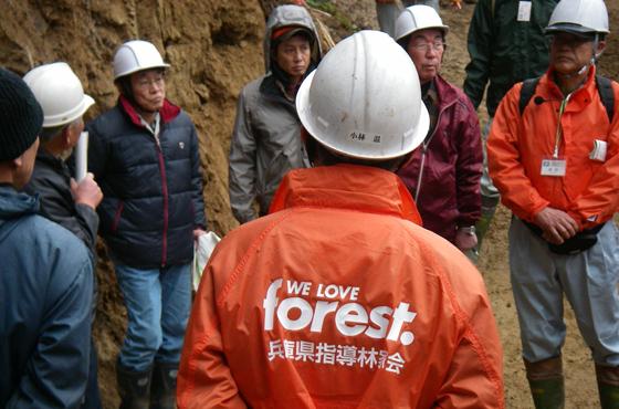 写真:ヘルメットを被りオレンジ色のジャンパーに身を包む小林さんの後ろ姿