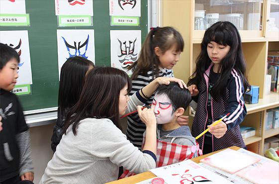 写真:中町北小学校の「隈取教室」で山根さんが生徒に隈取を施す。