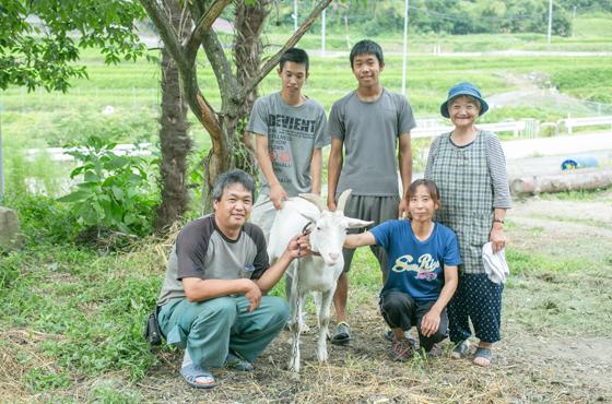ヤギのメーちゃんを囲む家族。前列が学さんと多恵さん夫婦。後列左から学さんの長男勇さん、次男良拡さん、今西さんの妻初子さん