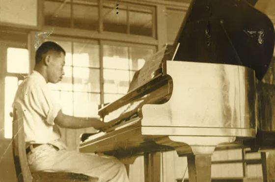 高校の音楽室でピアノの練習をする鈴木さん。まだ校歌のなかった新制高校で「全校生が一緒に歌える曲を」と依頼され宣揚歌を独学で作曲した。