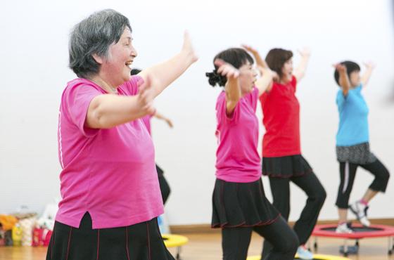 右腕が上がらず、膝も痛いが「ここに来ると楽しんでいるみんなにつられて体が動く」という67歳の糸長博子さん(手前)。
