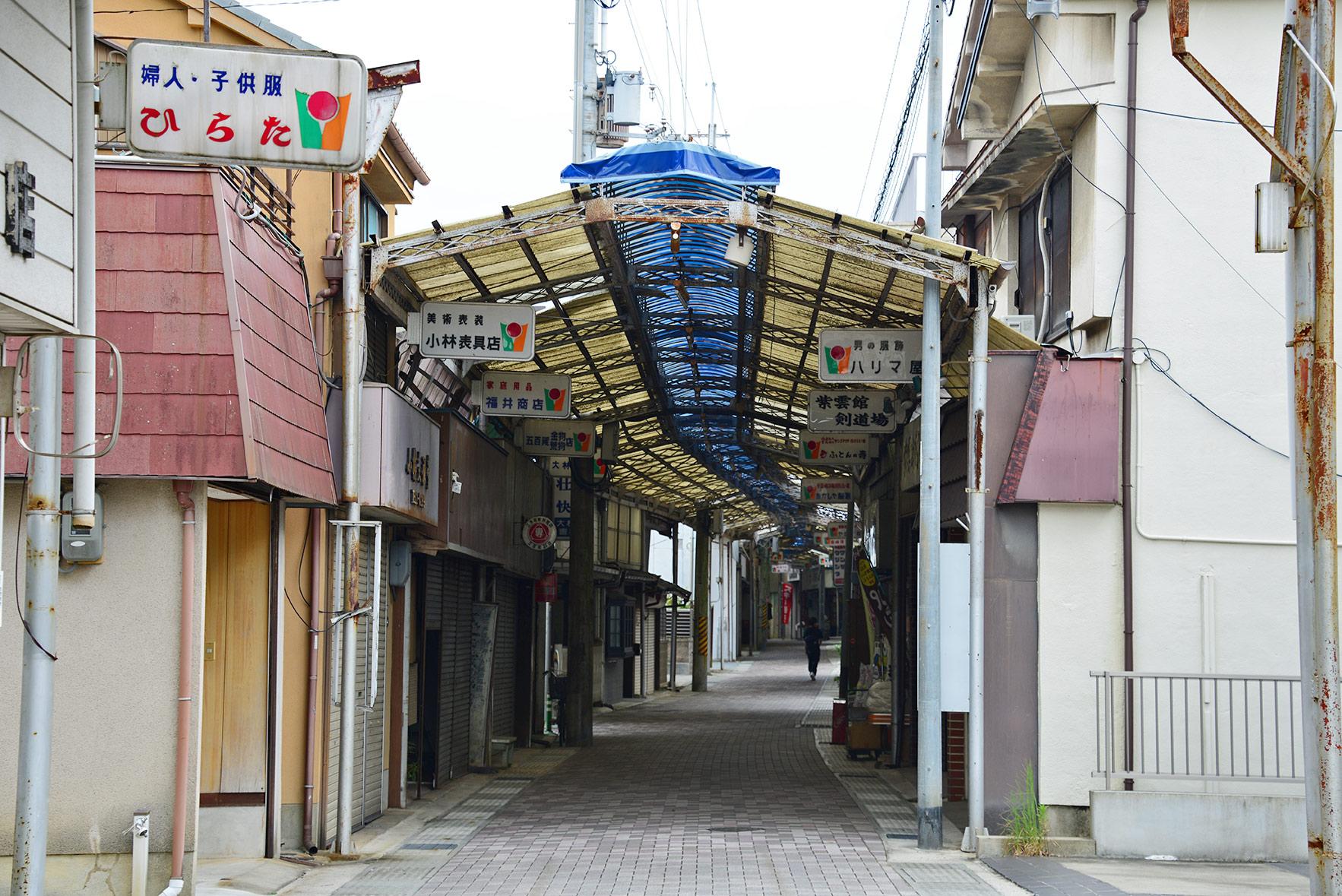 看板が上がっていても廃業した店舗があり、昼間でも多くのシャッターが下りているナメラ商店街。