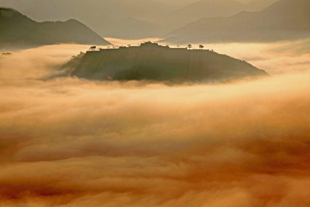 朝陽に照らさた雲海が黄金に光りシルエットが美しい竹田城跡