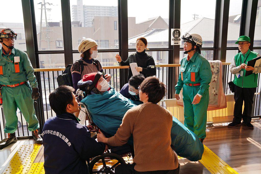 車椅子を抱えて階段を降りる等、身体障害者とその家族や支援者を対象とした避難訓練