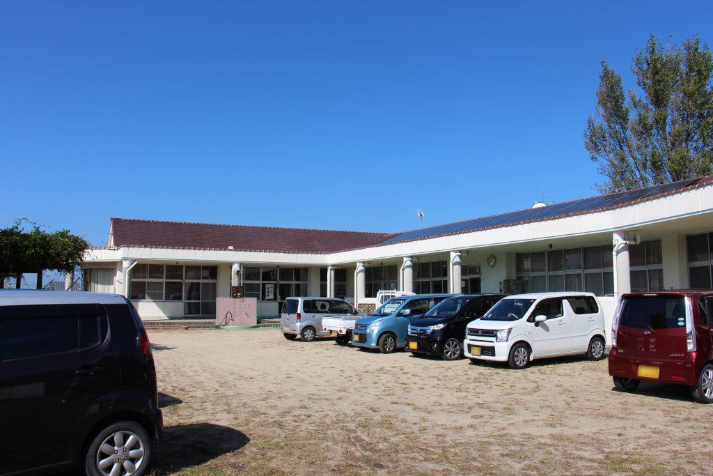尾崎ふれあい交流広場の拠点の一つ、ふれあい交流サロン『尾崎ガーデンズ』の営業場所である旧尾崎保育園。取材日当日は、ガーデンズも営業日であり、さらに展示が行われていたこともあって、園庭の駐車スペースには多くの車が止まっていた。