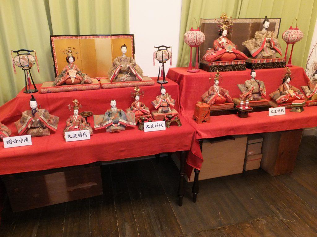 お雛さま展示の一部。各時代のお雛さまの展示のほか、地元の幼稚園児による絵画も一緒に展示。