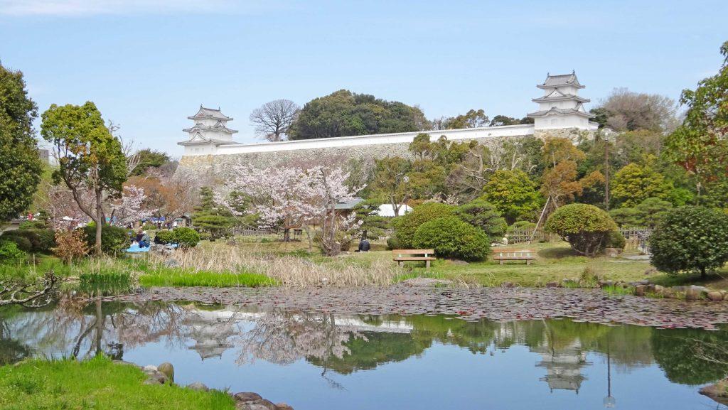 春の明石城(池の水面には桜と2つの櫓が写る)