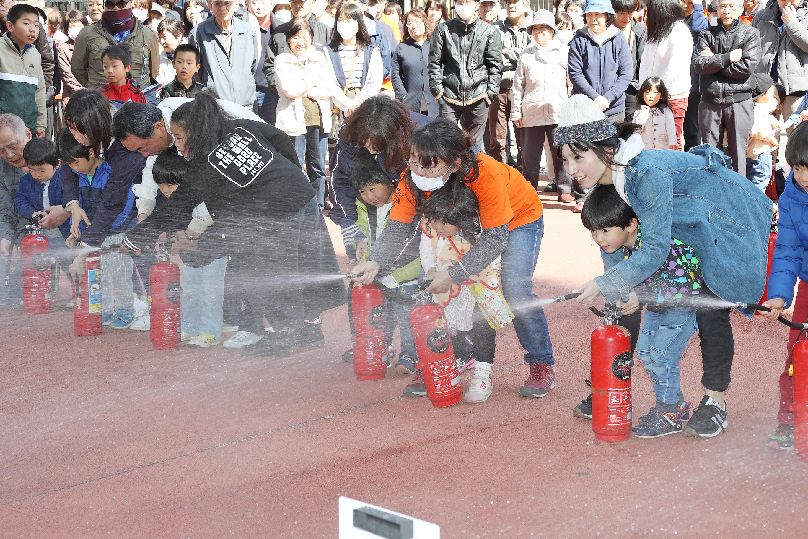 子どもたちも参加する防災訓練、消火器の使い方について、子どもから大人まで指導を受けている