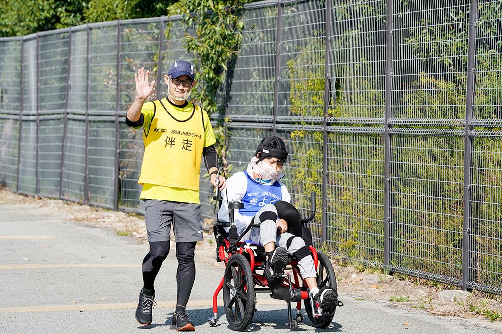 練習会で足こぎ車いすをこぐ聖憲さんと伴走ランナー