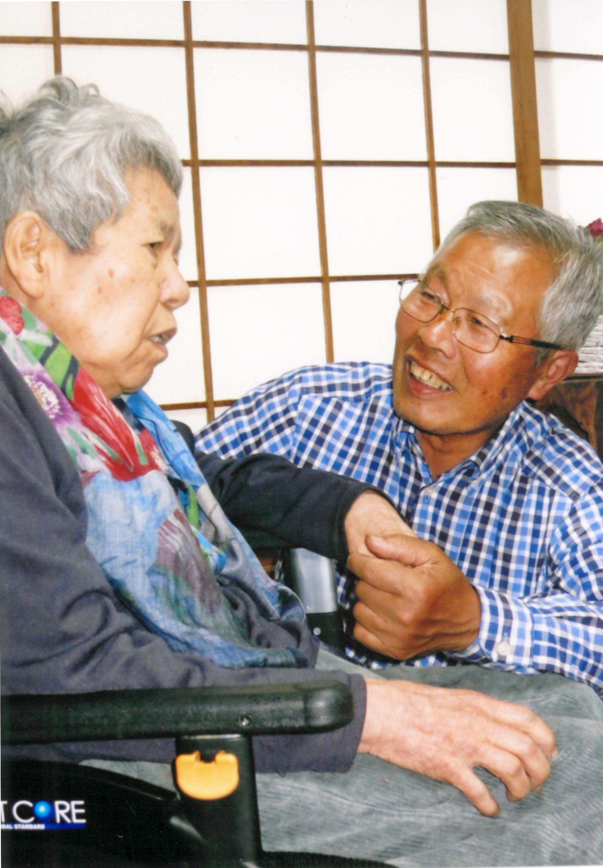 吉田さん夫妻笑顔で寄り添う吉田さん